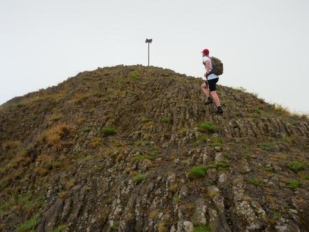 basalt: Hiker climbing on sharp peak of basalt formation. Long poles of cold basalt volcano.