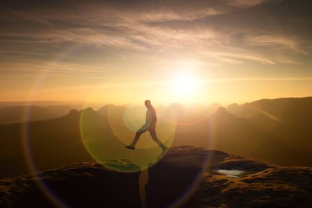 defect: Jumping hiker in black celebrate triumph Between Two rocky peaks. Wonderful daybreak. Strong lens defect Stock Photo