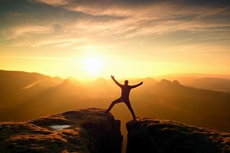 Hiker in black celebrate triumph between two rocky peaks. Wonderful daybreak in rocky mountains, heavy orange mist in deep valley