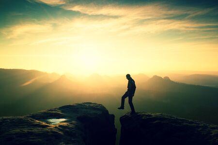 Crazy hiker in black is jumping between rocky peaks. Happy man. Wonderful daybreak in rocky mountains, heavy orange mist in deep valley. Miracle of nature