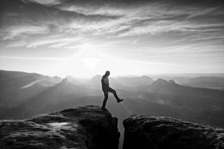 empires: Man in black jumping between rocky empires. Dreamy daybreak in sandstone mountains, heavy orange mist in deep valley.