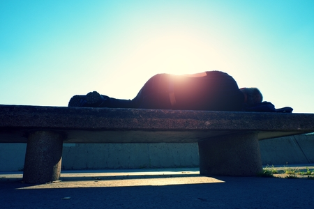 drank: Drank adult man rests on stone bench in the park, Sharp sun rays make contours around sleeping body.