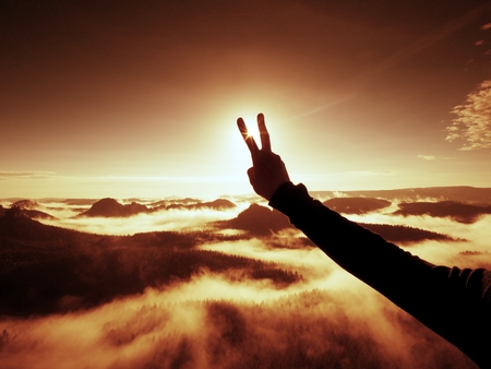 Man hand make victory to Sun. Misty daybreak in a beautiful hills. Peaks of hills are sticking out from foggy background, the fog is red and orange due to Sun rays. Stock Photo