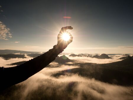Man hand touch Sun. Misty daybreak in a beautiful hills. Peaks of hills are sticking out from foggy background, the fog is red and orange due to Sun rays.