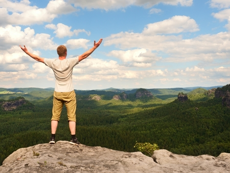 satisfy: Happy man with open rised  arms  Gesture of triumph. Satisfy hiker in grey shirt and trekking shorts on  sandstone cliff watching down to landscape. Stock Photo