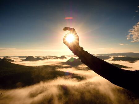 Man hand touch Sun. Misty daybreak in a beautiful hills. Peaks of hills are sticking out from foggy background, the fog is red and orange due to Sun rays.  Lens defects.