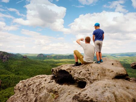 Father and son on mountain top watching into opened landscape. Long forest valley up to horizon.