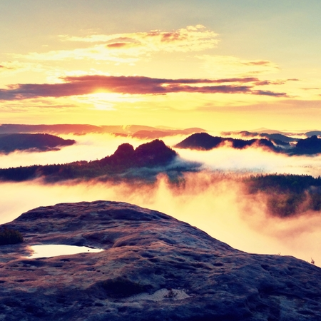 rocky peak: View over wet sandstone rocky peak into forest valley, daybreak Sun at horizon. Hills increased from foggy background Stock Photo