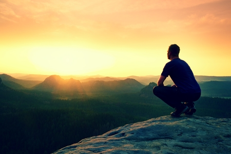 Tourist in squatting position on peak of sandstone rock and watching into colorful mist and fog in morning valley. Orange daybreak at horizon Imagens