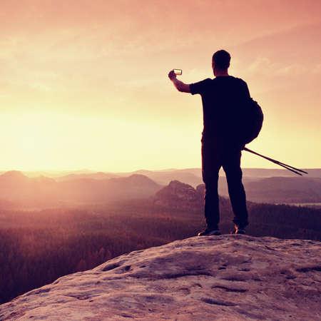 marvelous: Strong man hiker taking photo with smart phone at mountain peak. Marvelous daybreak.