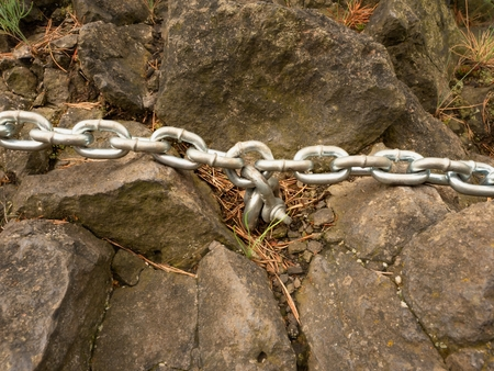 welded: Eye bolt with iron chain anchored into sandstone rock. Twisted chain of climber safety path fixed in block by screws snap hooks. Stock Photo