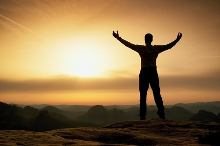 satisfy: Happy man with open raised arms Gesture of triumph. Satisfy hiker  silhouette on sandstone cliff watching down to landscape.
