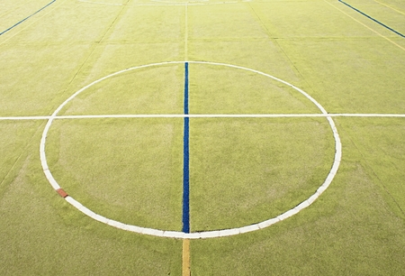 bounds: Circle in middle of court. Empty outdoor handball playground, plastic light green surface on ground and white blue bounds lines. Stock Photo