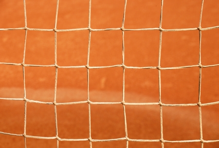 red clay: Old net with the ground and white line tennis court. Dry red clay. Light red crushed bricks surface on outdoor tennis ground
