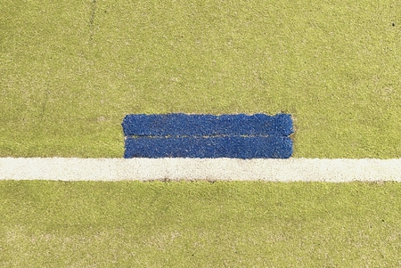 bounds: Colorful lines in empty outdoor handball playground, plastic light green surface on ground and white, red and blue lines bounds.