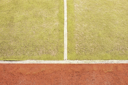 worn out: Border lines on court. Worn out green red hairy carpet on outside hanball playground. Floor of sports court with white marking lines.