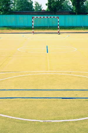 bounds: Empty outdoor handball playground, hairy green plastic surface on ground white and blue bounds lines.