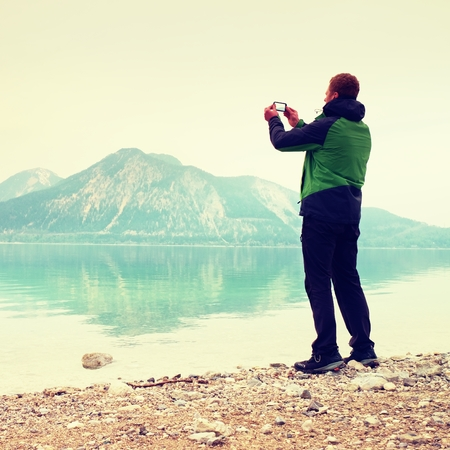 tall man: Tall man hold cellphone, take picture of autumn mountain lake scenery after rainy day. Vivid and vignetting effect. Poor lighting conditions. Stock Photo