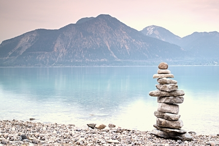 Balanced stone pyramide on shore of blue water of mountain lake. Blue mountains in water level mirror. Children built pyramid from pebbles.  Poor lighting conditions.