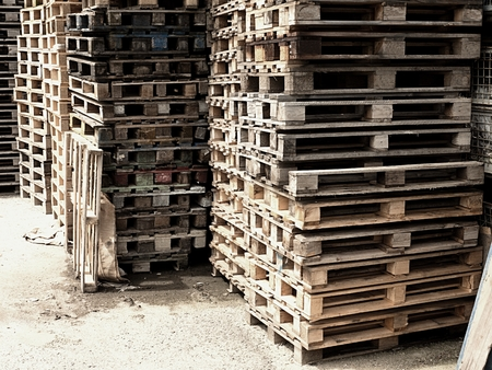 manufactured: Outside stock of old manufactured wooden standard euro pallets stored in pylons