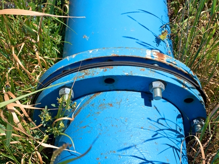 drain fly: Repaired big drink water pipes joined with new flanges blue and silver screws Stock Photo