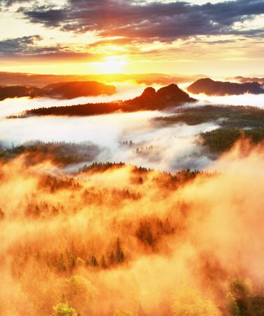 inversion: Red filter photo. Red daybreak. Misty daybreak in a beautiful hills. Peaks of hills are sticking out from foggy background, the fog is red and orange due to Sun rays.