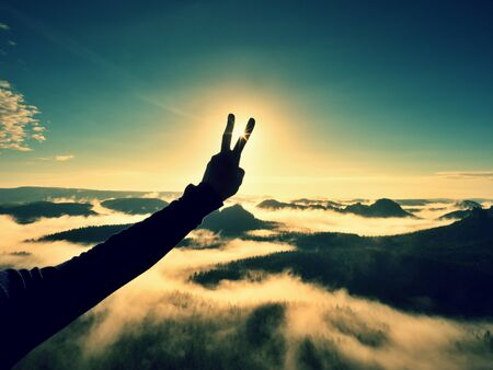 inversion: Man hand victory to make Sun. Misty daybreak in a beautiful hills. Peaks of hills are sticking out from foggy background, the fog is red and orange due to Suns rays. Stock Photo