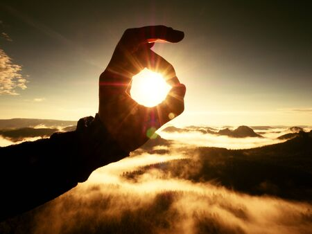 inversion: Man hand touch Sun. Misty daybreak in a beautiful hills. Peaks of hills are sticking out from foggy background, the fog is red and orange due to Sun rays.