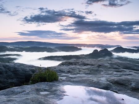 Landscape in water mirror. Misty awakening in beautiful mountains park. Peaks of hills in valley full of mist after heavy rain