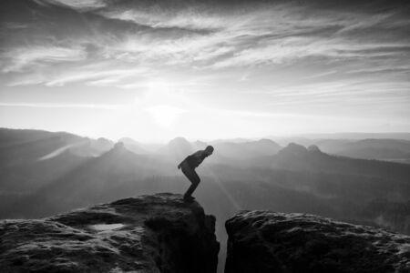 maniac: Crazy hiker in black is jumping between rocky peaks. Happy man. Wonderful daybreak in rocky mountains, heavy orange mist in deep valley. Miracle of nature