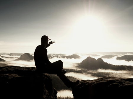 crack climbing: Hiker in black sportswear is sitting on cliffs edge. Man taking nature photos by smart phone while sunrise above mountains. Vivid effect