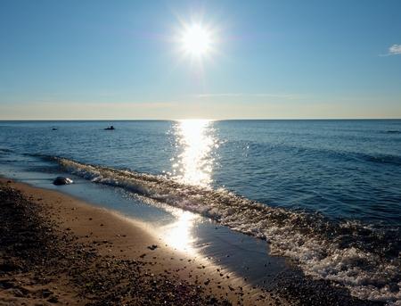 Romantic morning at sea,  smooth wavy sea. Horizon with hot sun rays. Stock Photo