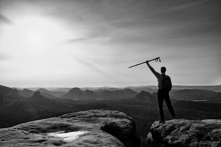 the next step: Tourist with poles in hands stand on rock watching  for next step. Sunny spring daybreak in mountains.Vignetting effect..