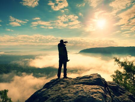 Photographer with folden tripod on cliff shadowing eyes and thinking. Heavy fogy landscape, misty sunrise in  beautiful valley below
