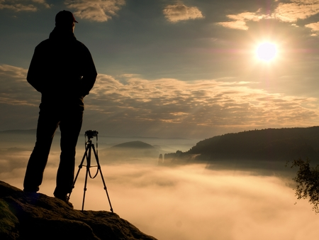 documenting: Photographer on cliff. Nature photographer Takes photos with mirror camera on the peak of rock. Dreamy fogy landscape, spring orange pink misty sunrise in a beautiful valley below. Stock Photo