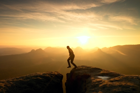 Young crazy man jump on mountain peak. Silhouette of jumping man and beautiful sunset sky. Vintage effect, lens defect.