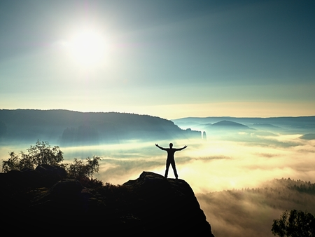 Happy man gesture of triumph with hands in the air. Funny hiker with raised arms on peak of sandstone rock in national park. Vivid and strong vignetting effect. Stock Photo