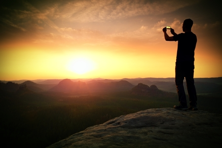 tall man: Tall man hiker is taking photo by smart phone on the peak of mountain at sunrise.
