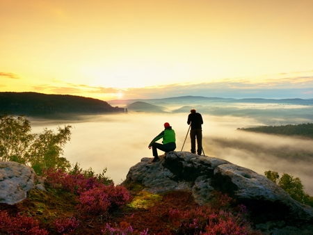 documenting: Hiker and photo enthusiast stay with tripod on cliff and takes photos. Dreamy fogy landscape, blue misty sunrise in a beautiful valley below