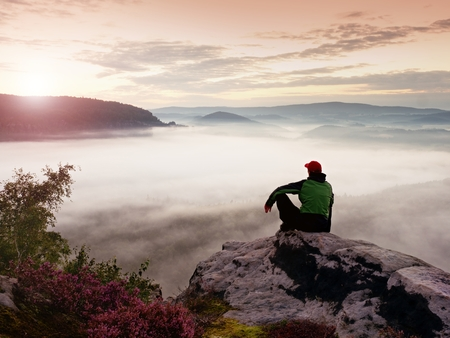 a wonderful world: Man tourist sit on rock empire. View point with heather and branches above misty valley. Sunny daybreak in rocky mountains. Stock Photo