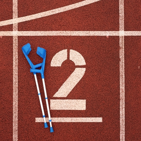 pierna rota: Medicine crutch for broken leg. Number two. Big white track number two on red rubber racetrack. Gentle textured running racetracks in athletic stadium.