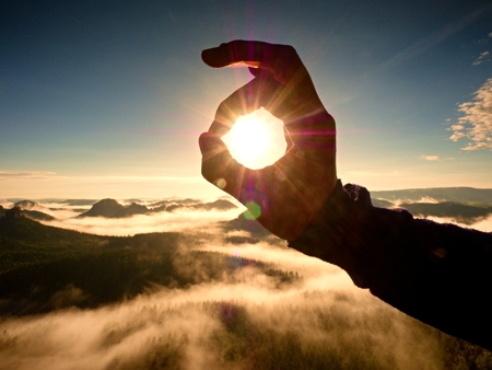 Man hand touch Sun. Misty daybreak in a beautiful hills. Peaks of hills are sticking out from foggy background, the fog is red and orange due to Suns rays. Stock Photo