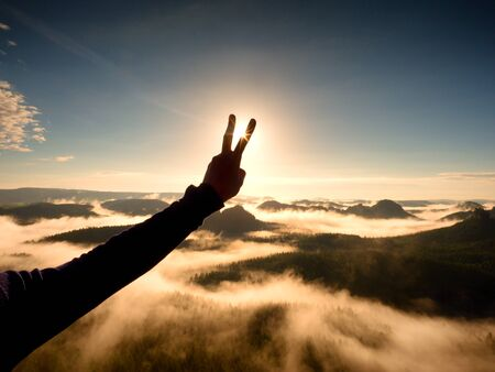 Man hand victory to make Sun. Misty daybreak in a beautiful hills. Peaks of hills are sticking out from foggy background, the fog is red and orange due to Suns rays. Stock Photo