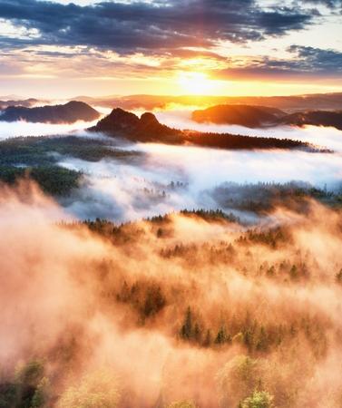 Růžová slunce v nádherné pískovcové Rocky Mountain. Ostré vrcholy zvýšil z mlhavé pozadí, mlha je červená a oranžová kvůli horkých slunečních paprsků. Reklamní fotografie