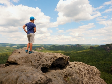empires: Alone Hiker boy in blue cap stand on the peak of sandstone rock in rock empires park and watching over this valley Sun. Beautiful nature
