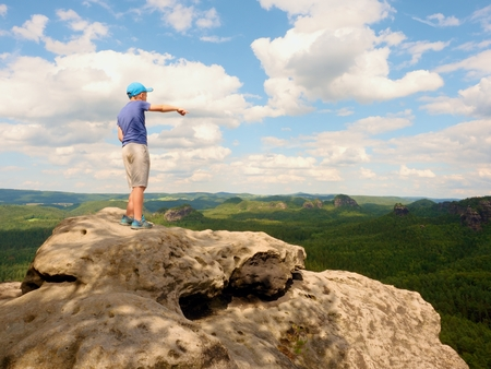 strip shirt: Alone Hiker boy in blue cap stand on the peak of sandstone rock in rock empires park and watching over this valley Sun. Beautiful nature
