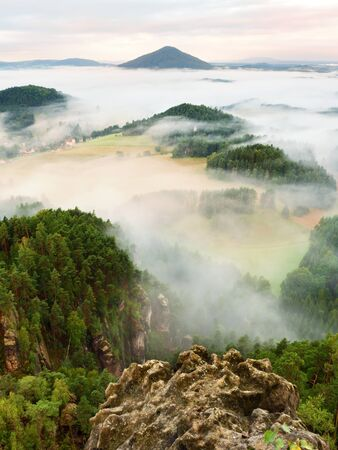 increased: Spring misty landscape. Morning in beautiful hills of natural park. Rocky peaks Increased from creamy heavy fog.