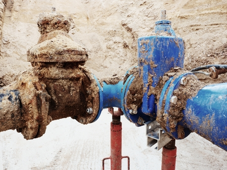 repaired: Old big drink water pipes joined with new blue gate valves and reduction joint members. Finished repaired piping waiting for covering by clay. Extreme kind of corrosion, metal corroded texture.