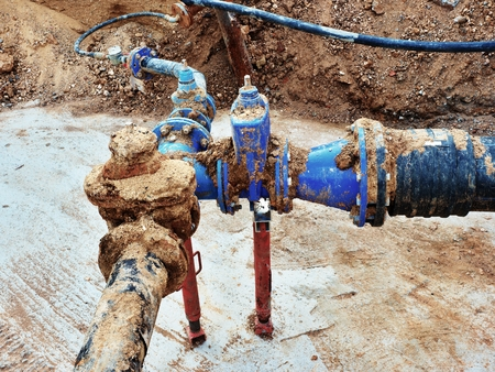 ductile: Old big drink water pipes joined with new blue gate valves and reduction joint members. Finished repaired piping waiting for covering by clay. Extreme kind of corrosion, metal corroded texture.