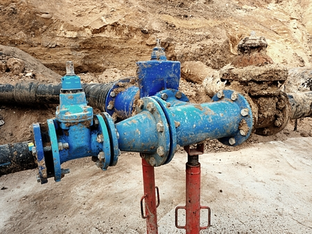 metal corrosion: Old big drink water pipes joined with new blue gate valves and reduction joint members. Finished repaired piping waiting for covering by clay. Extreme kind of corrosion, metal corroded texture.